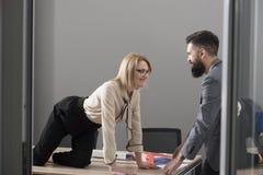 办公室浪漫史概念 性感的秘书在办公室诱惑上司 桌面看看的女实业家有胡子的商人 人 免版税库存图片