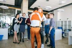 办公室浪漫史概念 拥抱在工作的两个混合的族种恋人 免版税库存图片