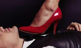 办公室爱情小说 在红色鞋子的妇女的腿 免版税库存图片