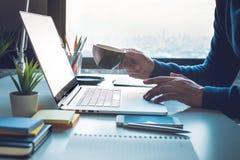 办公室生活概念用人饮用的咖啡和使用在窗口的计算机膝上型计算机 免版税库存图片