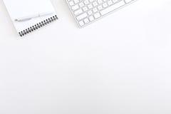 办公室白色表有键盘老鼠和笔记薄顶视图 库存照片