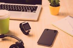 办公室设定 关闭两台膝上型计算机、片剂和一smartwatch在一张木办公室桌上 免版税图库摄影