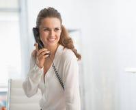 办公室谈的电话的现代女商人 免版税库存图片
