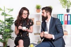 办公室谣言 办公室咖啡 夫妇工友放松咖啡休息 与与同事的份额咖啡 挥动的同事 免版税图库摄影