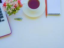 办公室辅助部件包括膝上型计算机、笔记本、红色铅笔、咖啡杯、计算器和花在白色背景 库存图片