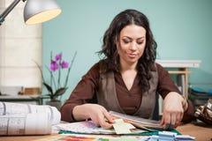办公室采摘颜色的建筑师从在她的书桌上的卡片 免版税图库摄影