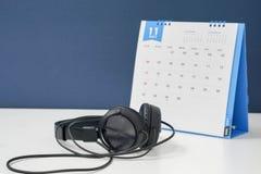办公室11月日历和耳机 库存照片
