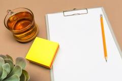 办公桌桌用剪贴板颜色贴纸茶和多汁植物 模板的嘲笑 顶视图 库存照片