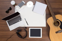 办公桌背景声学吉他和耳机记录 免版税库存照片