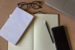 办公桌顶视图有空白的白色笔记本的,眼力玻璃、手机、笔和片剂在黄柏制表背景 免版税图库摄影