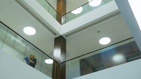 办公楼内部地板与玻璃细长立柱和妇女步行的 股票录像