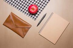 办公用品和苹果的混合在棕色桌上镶边了织品和包装纸背景 免版税库存照片
