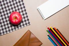 办公用品和苹果的混合在棕色桌上镶边了织品和包装纸背景 库存图片