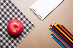 办公用品和苹果的混合在棕色桌上镶边了织品和包装纸背景 免版税图库摄影