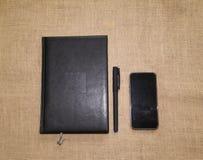办公用品汇集-笔记本和电话在棕色粗麻布 免版税库存图片