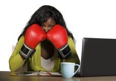 办公计算机书写工作和交涉战斗注重的拳击手套的年轻愤怒和恼怒的美国黑人的女商人 图库摄影