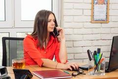 办工室职员在电话谈话并且寻找关于计算机的信息 库存照片