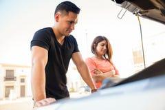 年轻加上一辆残破的汽车 免版税库存照片
