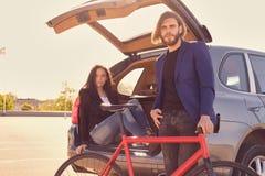 加上唯一速度在有开放树干的汽车附近骑自行车 免版税库存图片