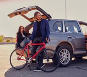 加上唯一速度在有开放树干的汽车附近骑自行车 免版税图库摄影