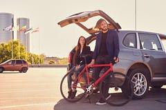 加上唯一速度在有开放树干的汽车附近骑自行车 库存照片
