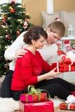 年轻加上在圣诞树前面的礼物 免版税库存照片