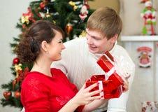 年轻加上在圣诞树前面的礼物 免版税库存图片
