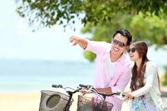 年轻加上在海滩的自行车 免版税库存照片