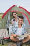 加上坐在他们的帐篷之外的地图 免版税图库摄影