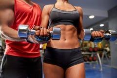 年轻加上屈曲在健身房的哑铃肌肉 免版税图库摄影