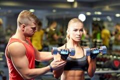 年轻加上屈曲在健身房的哑铃肌肉 免版税库存照片