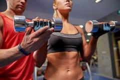 年轻加上屈曲在健身房的哑铃肌肉 免版税库存图片