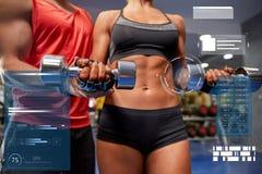年轻加上屈曲在健身房的哑铃肌肉 图库摄影