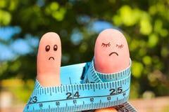 加上手指艺术米 概念人是稀薄的,妇女是肥胖的 免版税库存图片