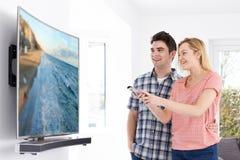 年轻加上新的弯曲的屏幕电视在家 库存照片