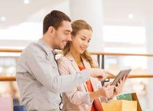 加上片剂个人计算机和在购物中心的购物袋 库存图片