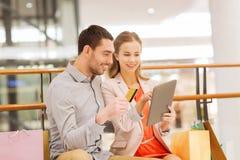 加上片剂个人计算机和在购物中心的购物袋 免版税库存照片