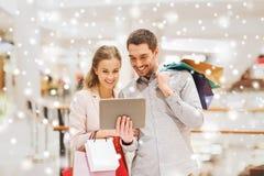 加上片剂个人计算机和在购物中心的购物袋 免版税库存图片
