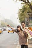 年轻加上称赞一辆计程车的购物袋在北京 免版税库存图片