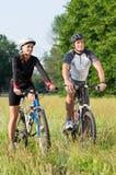 年轻加上自行车在草甸 库存图片