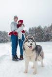 年轻加上走在冬天的一条多壳的狗停放,男人和妇女拥抱 免版税库存照片