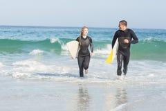 加上运行在海滩的冲浪板 免版税库存图片