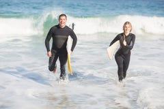 加上运行在海滩的冲浪板 免版税库存照片