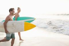 加上运行在海滩的冲浪板 图库摄影