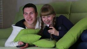 年轻加上酒观看的喜剧玻璃在电视和笑上的 股票录像