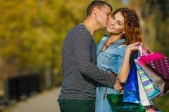 年轻加上购物袋在公园在秋天 图库摄影