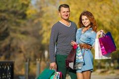年轻加上购物袋在公园在秋天 库存图片