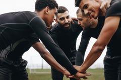 加入在杂乱的一团的足球运动员手谈论比赛战略 弯曲今后在杂乱的一团的低角度观点的足球运动员 免版税库存照片