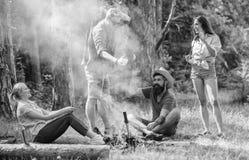 加入夏天野餐 获得的公司乐趣,当烤在棍子时的香肠 见面在篝火附近的朋友停留和 免版税库存照片