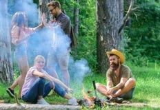 加入夏天野餐 见面在篝火附近的朋友停留和准备烤了香肠快餐自然背景 库存图片